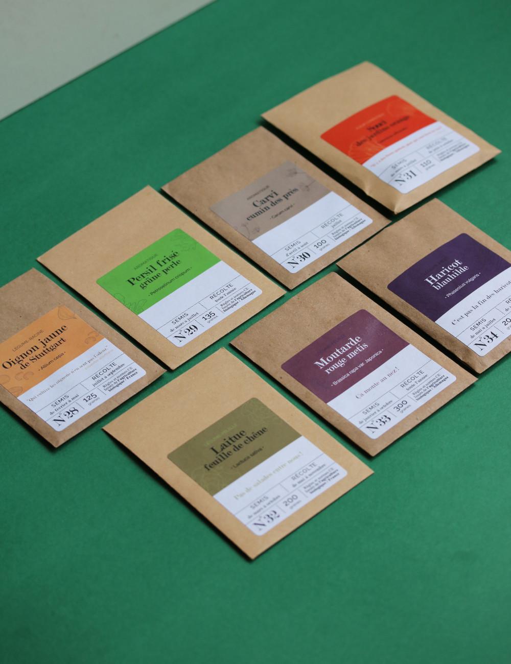 sachet de graines personnalisés en kraft alignés sur une boite en carton : carvi, oignon Stuttgart, souci orange des jardin, haricot blauhilde, moutarde metis, laitue feuille de chene